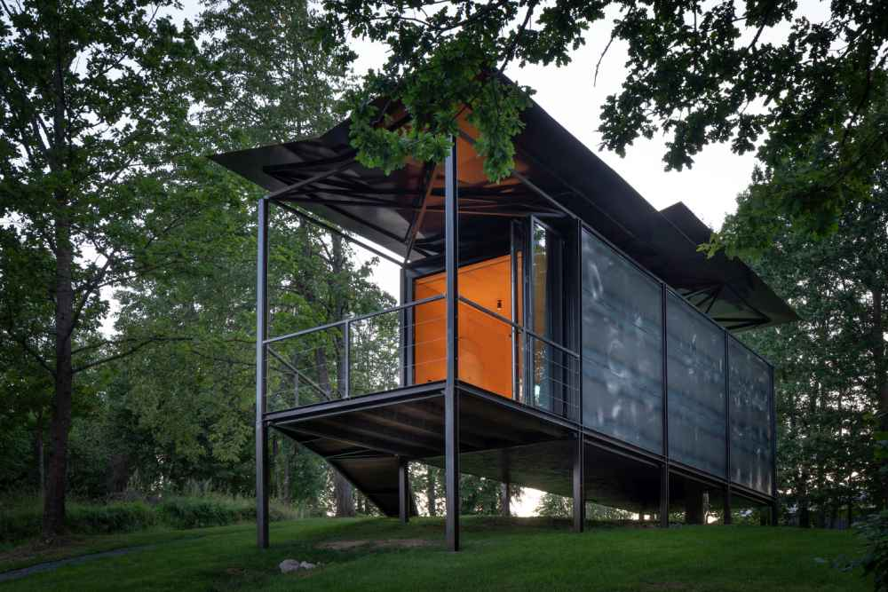The cabin is raised on slender columns/ legs of different heights made of metal