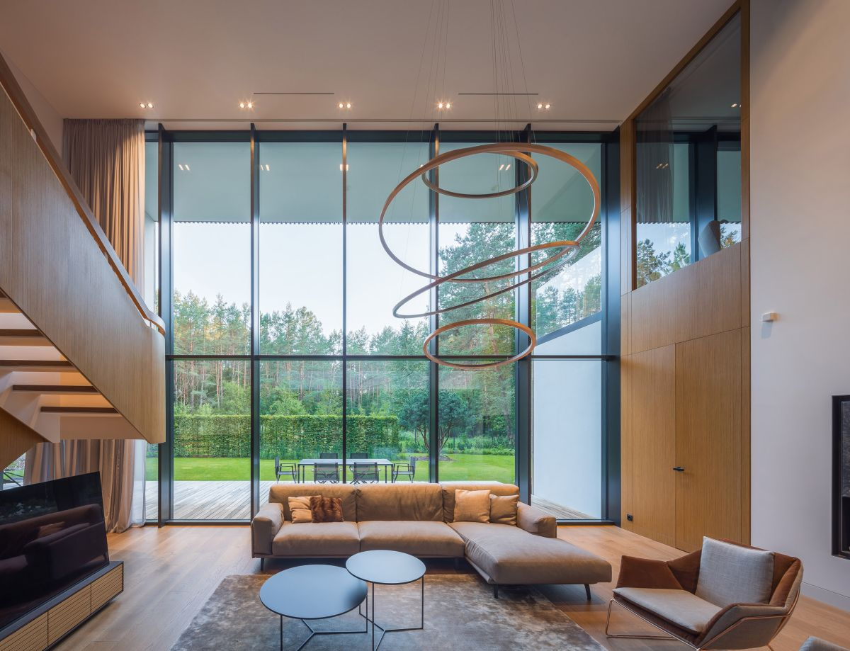 A modern sectional sits at the center of the living room and is complemented by a sculptural chandelier