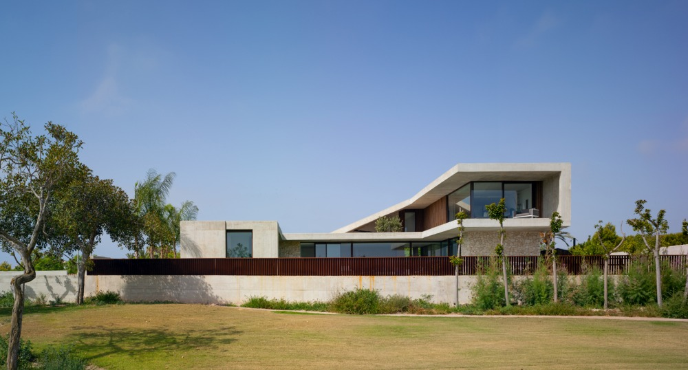 The upper floor follows the slope and cantilevers over the bedroom area