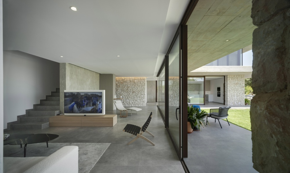 Large glazed walls and sliding glass doors maintain a close connection between the indoor and the outdoor areas