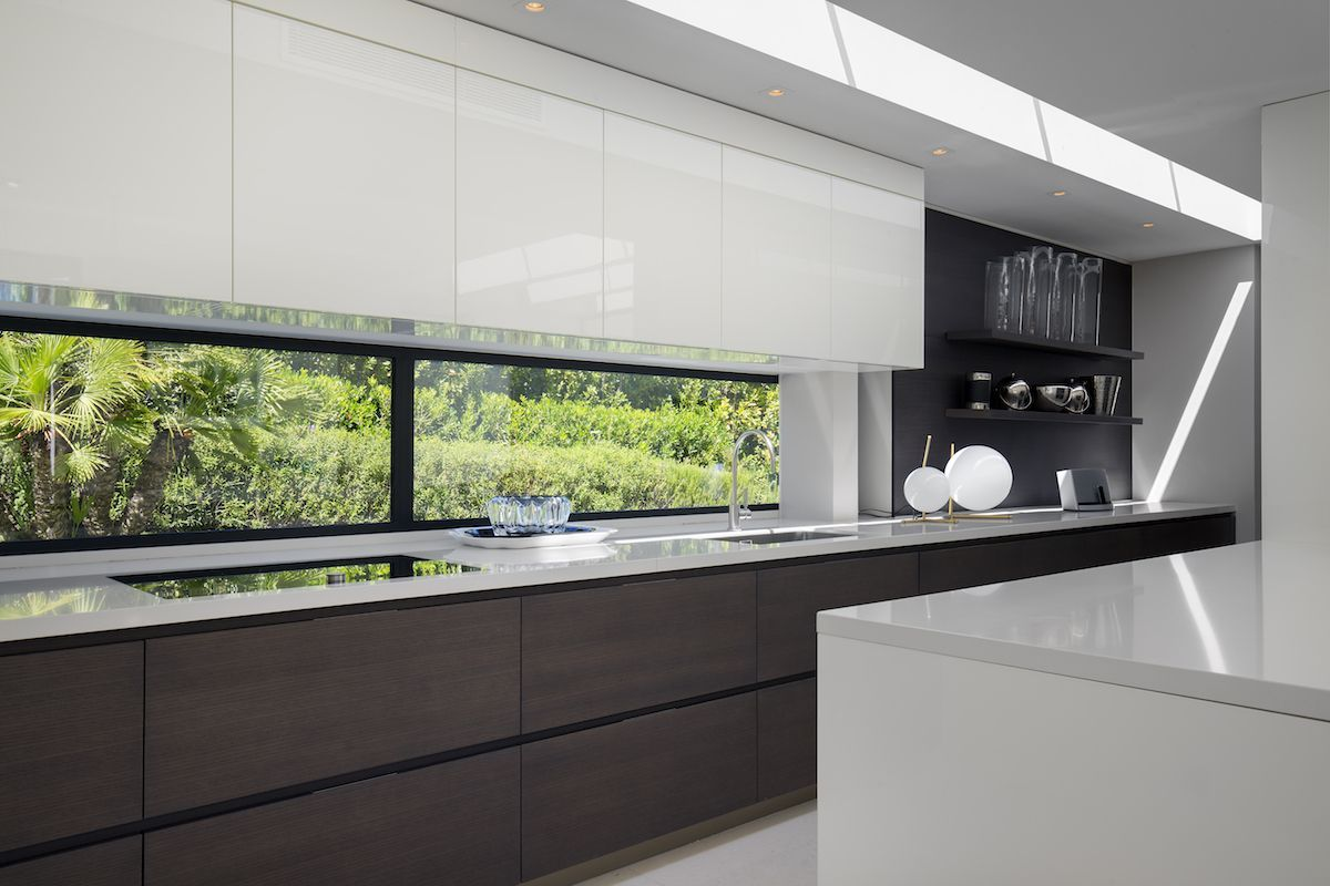 The kitchen has a window backsplash with a view of the garden. It brings in light as well as color