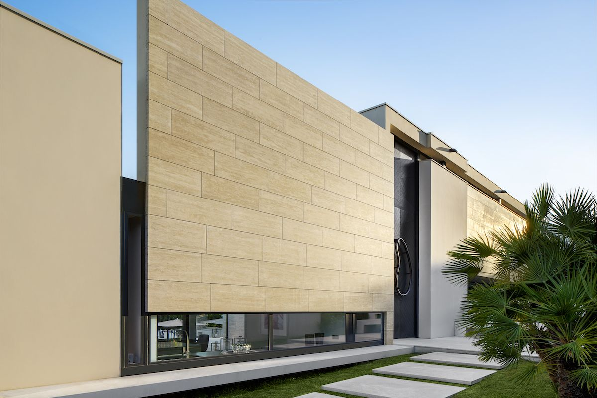 The street-facing facade is solid and mostly closed, featuring vertical and horizontal openings that let light in specific areas of the house