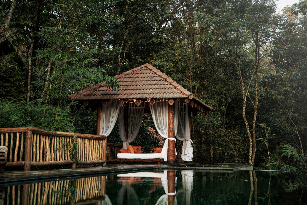 This beautiful gazebo by the pool has clay tile roof and sturdy log rafters