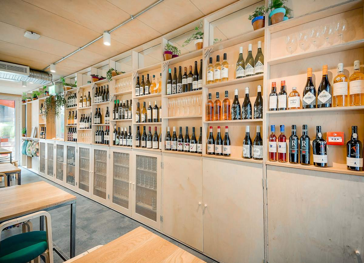 The walls of the bar feature lots of open shelves with wine bottles and glasses carefully displayed and stored on them
