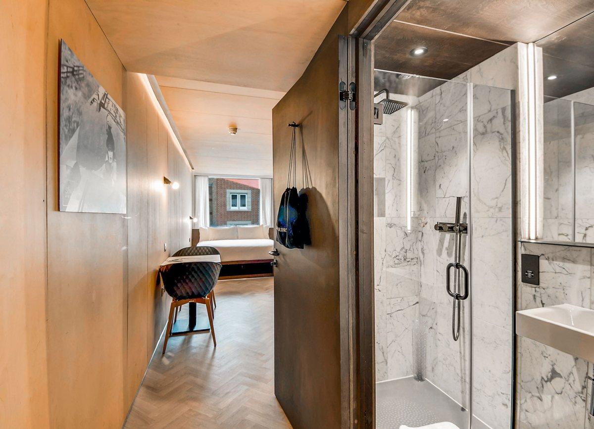 The bathroom has a walk-in shower with white marble tiles on the walls and a glass door