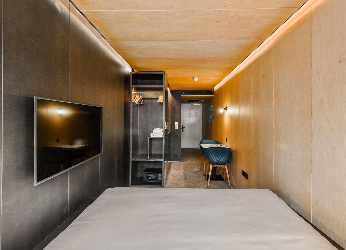 Each room has a bed, a bathroom, a small kitchen, a table with chairs, a storage closet and a wall-mounted TV