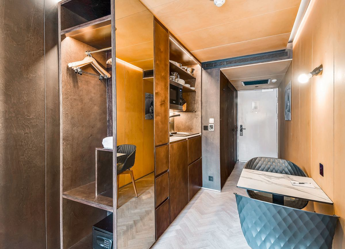 A tall mirror attached to the side of the built-in closet helps the narrow room appear brighter and larger