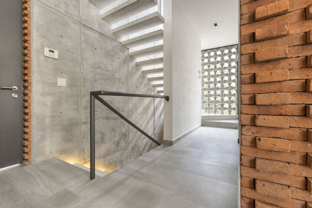 The guest area has an alternative entrance and a linear staircase with a chic and urban vibe