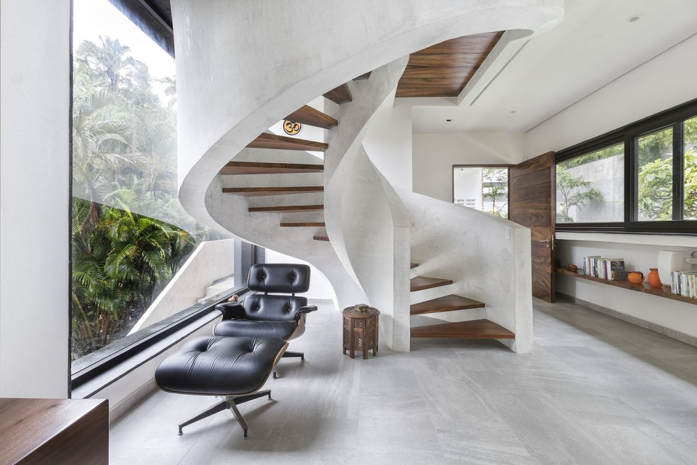 The main entrance is dominated by a majestic spiral staircase made out of flat concrete and wood