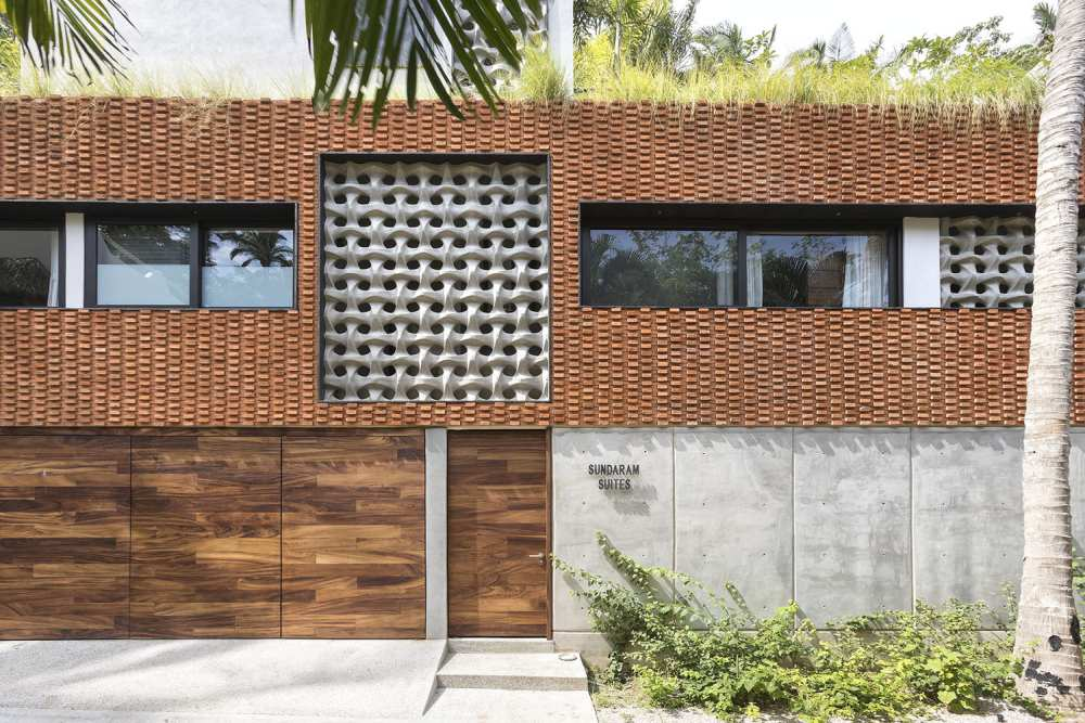 The facade of the house is a quirky mix of concrete, wood and bricks with contrasting colors, textures and patterns