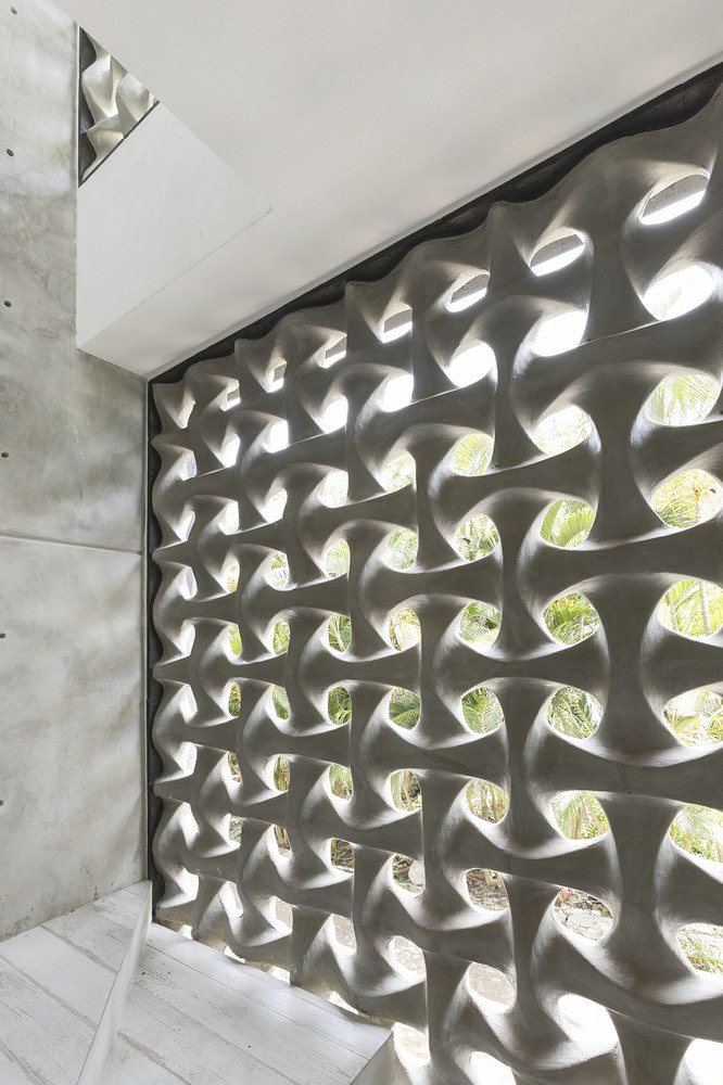 The sculptural concrete wall sections let light filter through and are a stylish alternative to regular windows