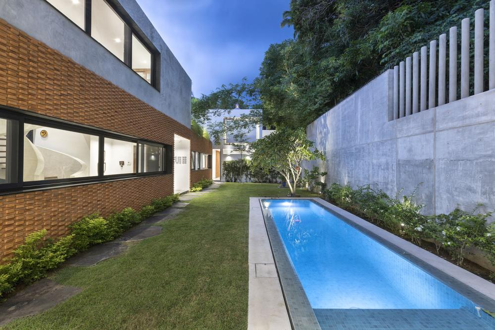 The main living area has access to a small garden with a rectangular pool pushed against the back wall