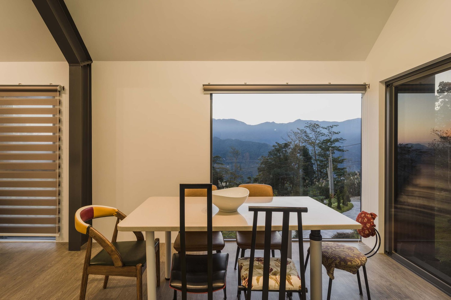 A square-shaped dining table with diverse chairs around it creates a very casual and friendly vibe