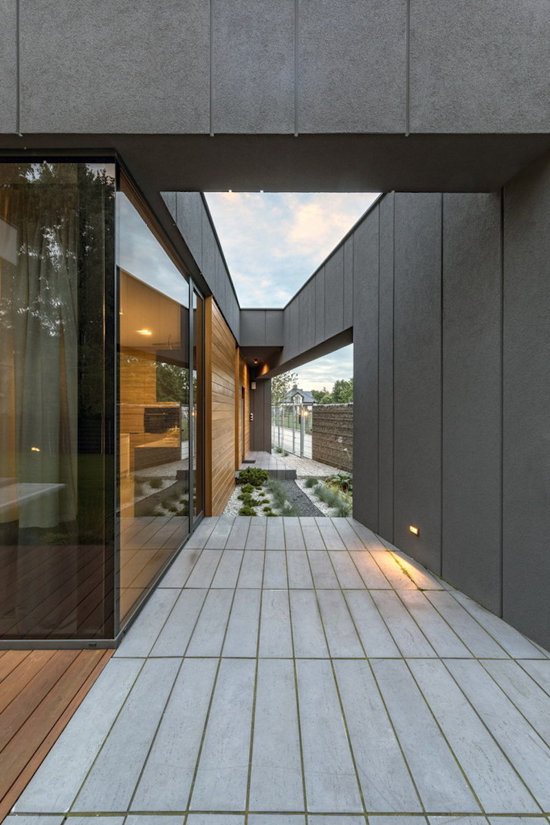 A freestanding wall offers privacy from the road and shelters a small terrace between in and the kitchen area