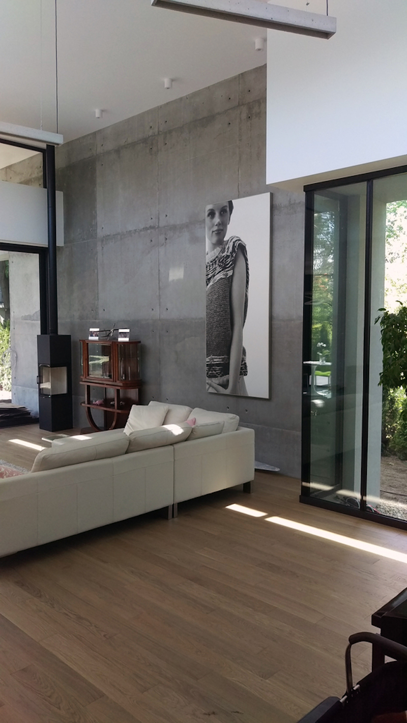 The living room has an exposed concrete wall which serves as a backdrop for the fireplace and artwork