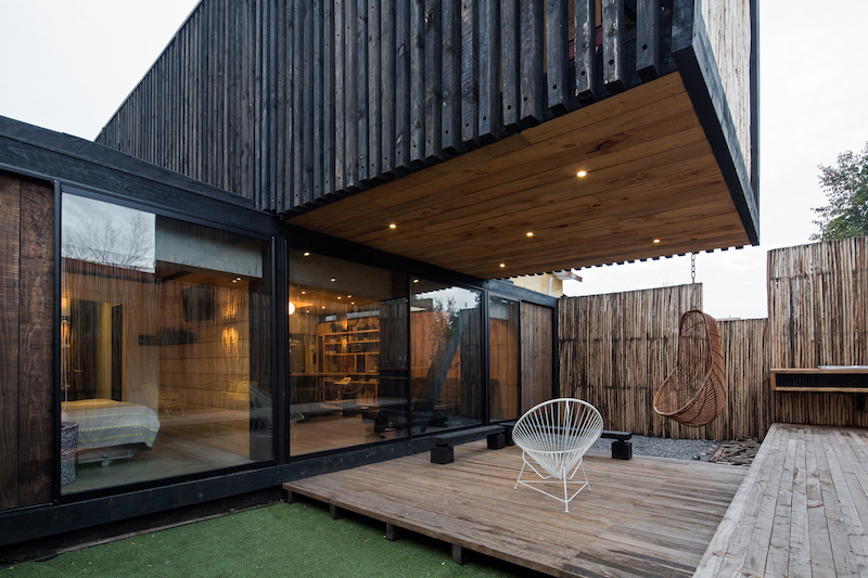 The deck serves as an extension of the interior living spaces and is protected by the cantilevered volume