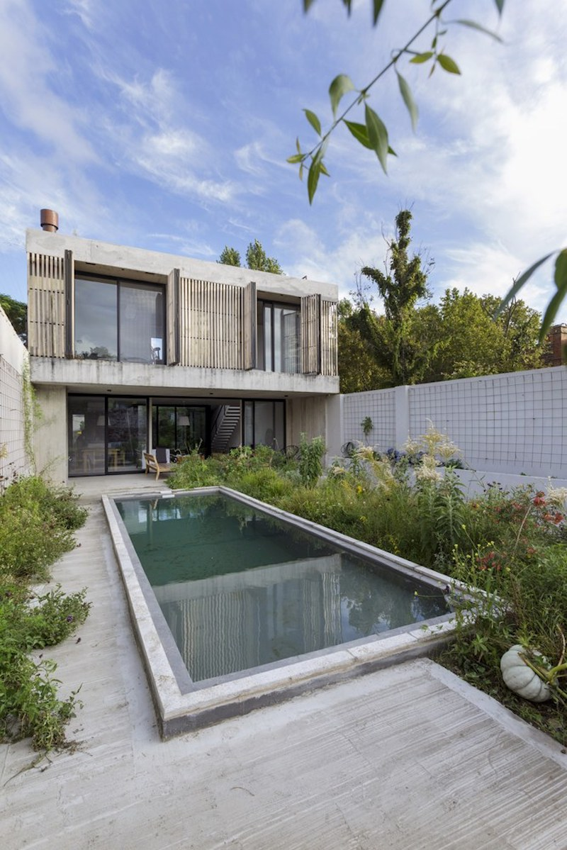 The swimming pool is positioned at the center of the yard, with greenery growing around it