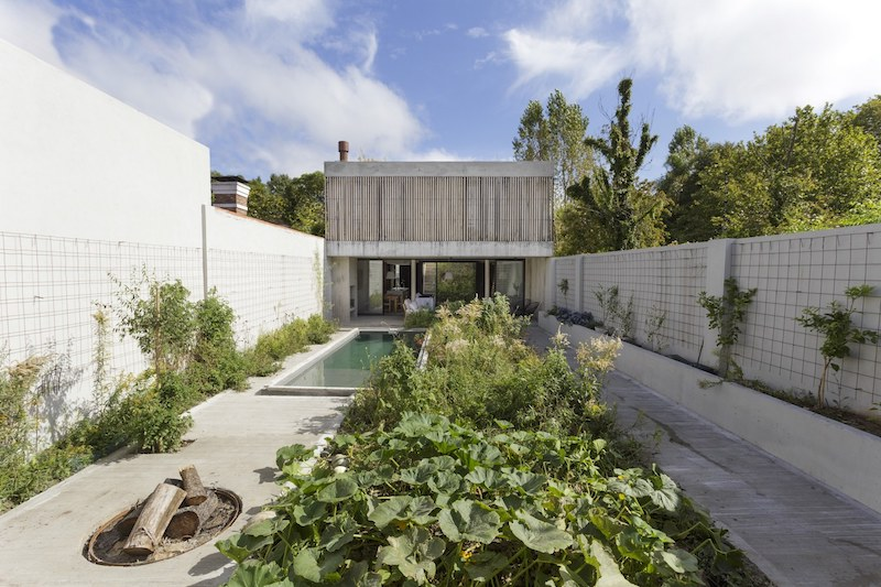 The house sits on a plot between two existing buildings, with a long and narrow courtyard at the back