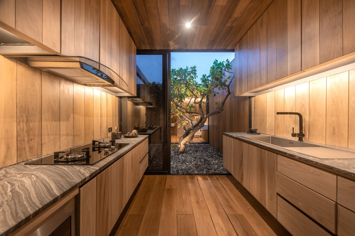 The kitchen has cabinets on either side and the internal courtyard at the rear