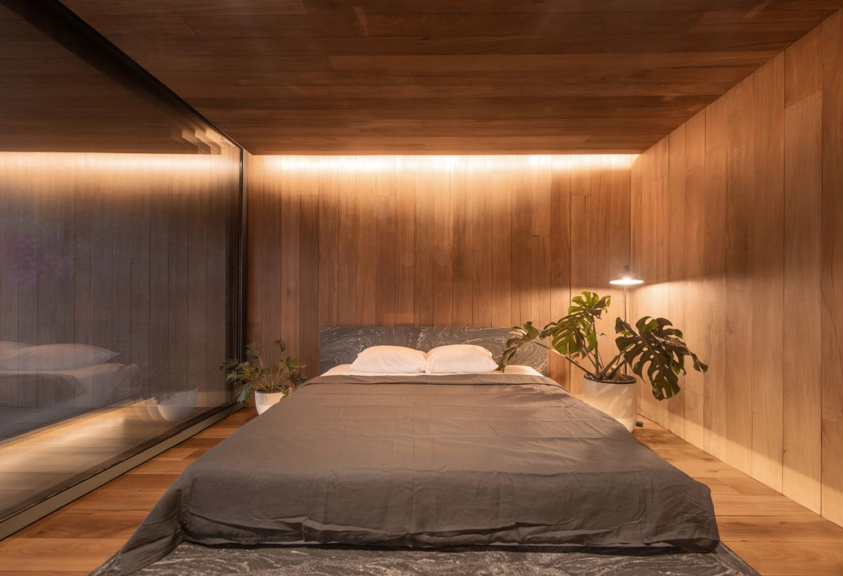 The bedroom is minimalist and features subtle accent lighting and very little furniture