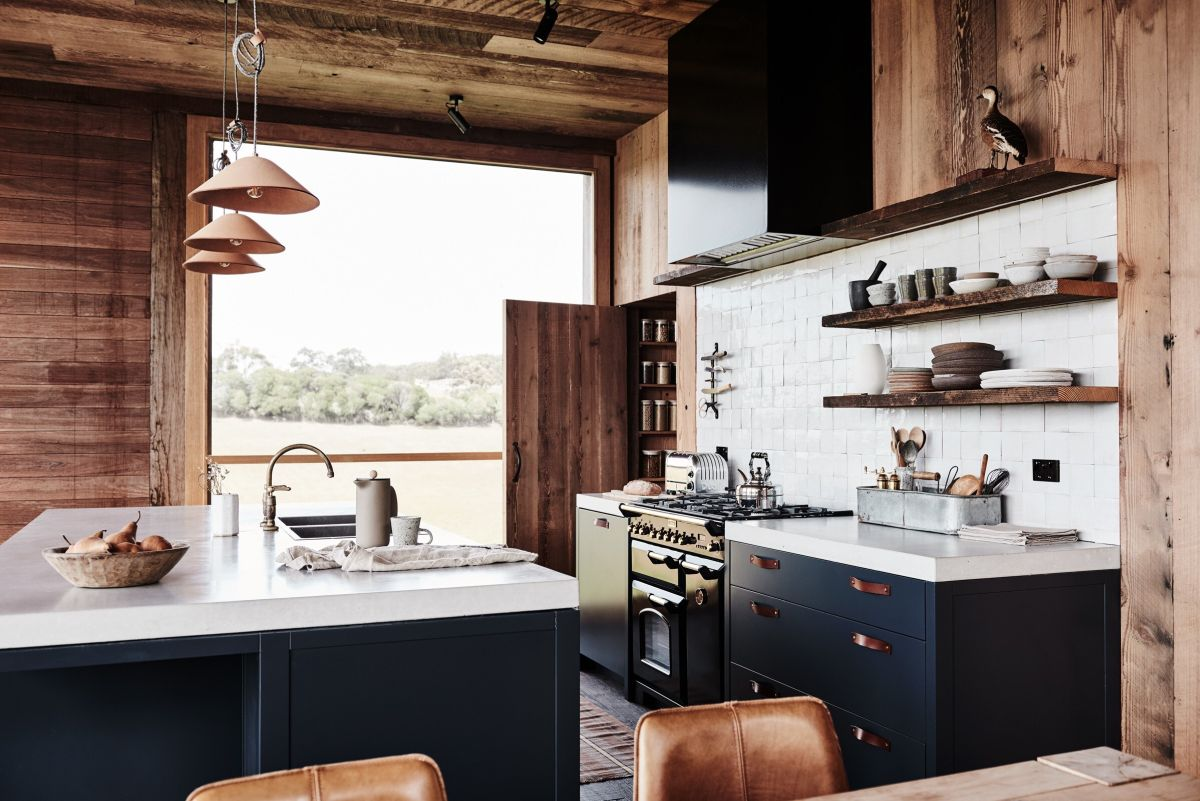 The kitchen is big and has a large island with stylish pendant lamps that illuminate it from above