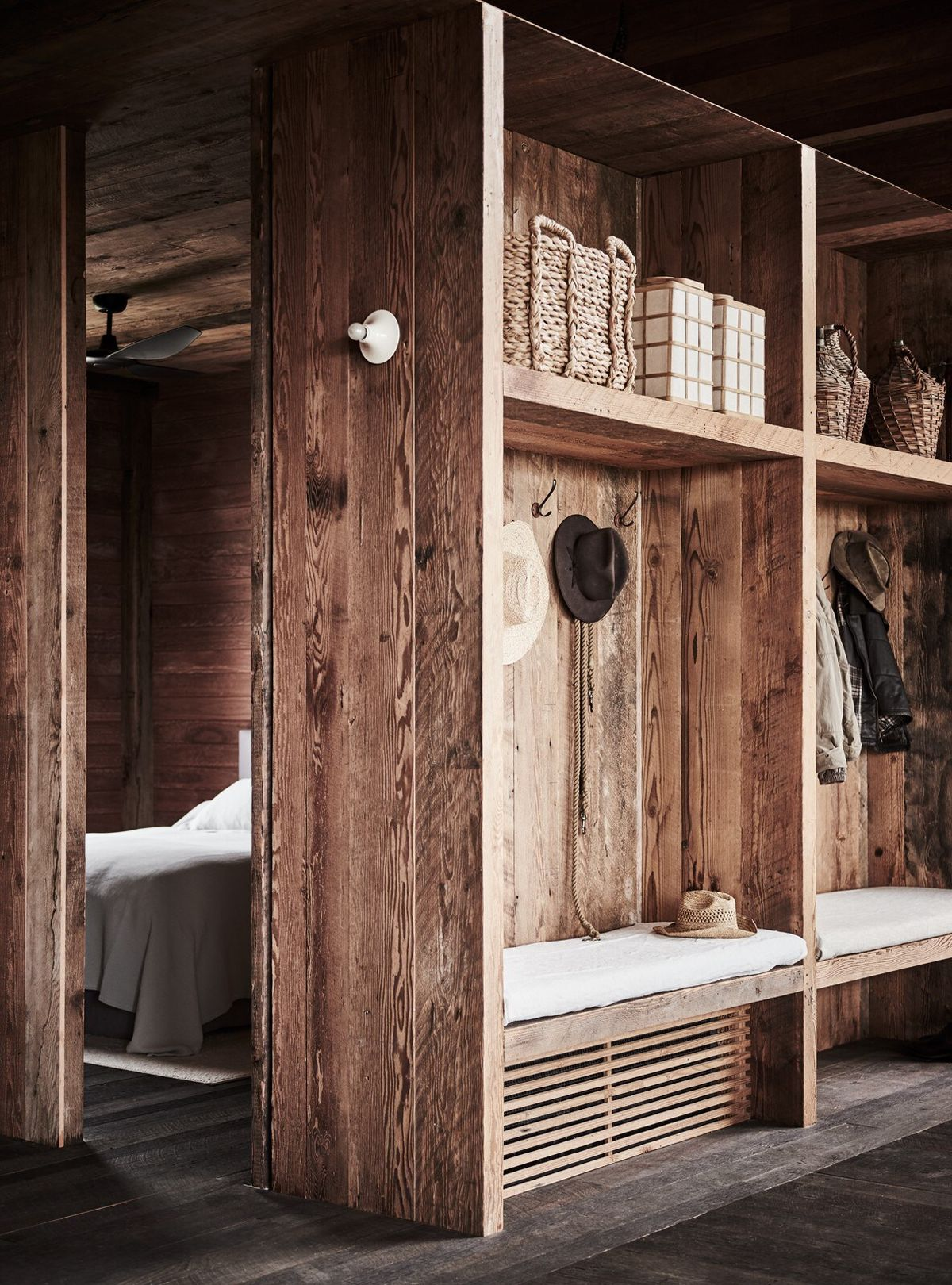 The entryway is marked by a set of small benches and a set of shelves and storage hooks built into one of the walls