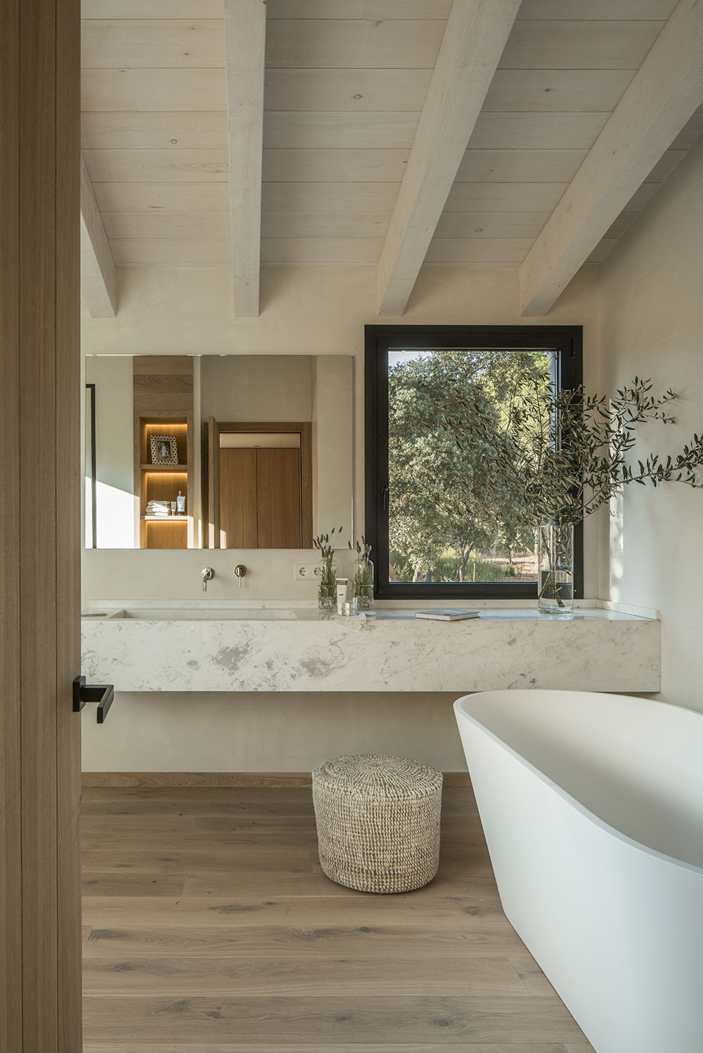The bathtub affords a view of the olive trees outside.