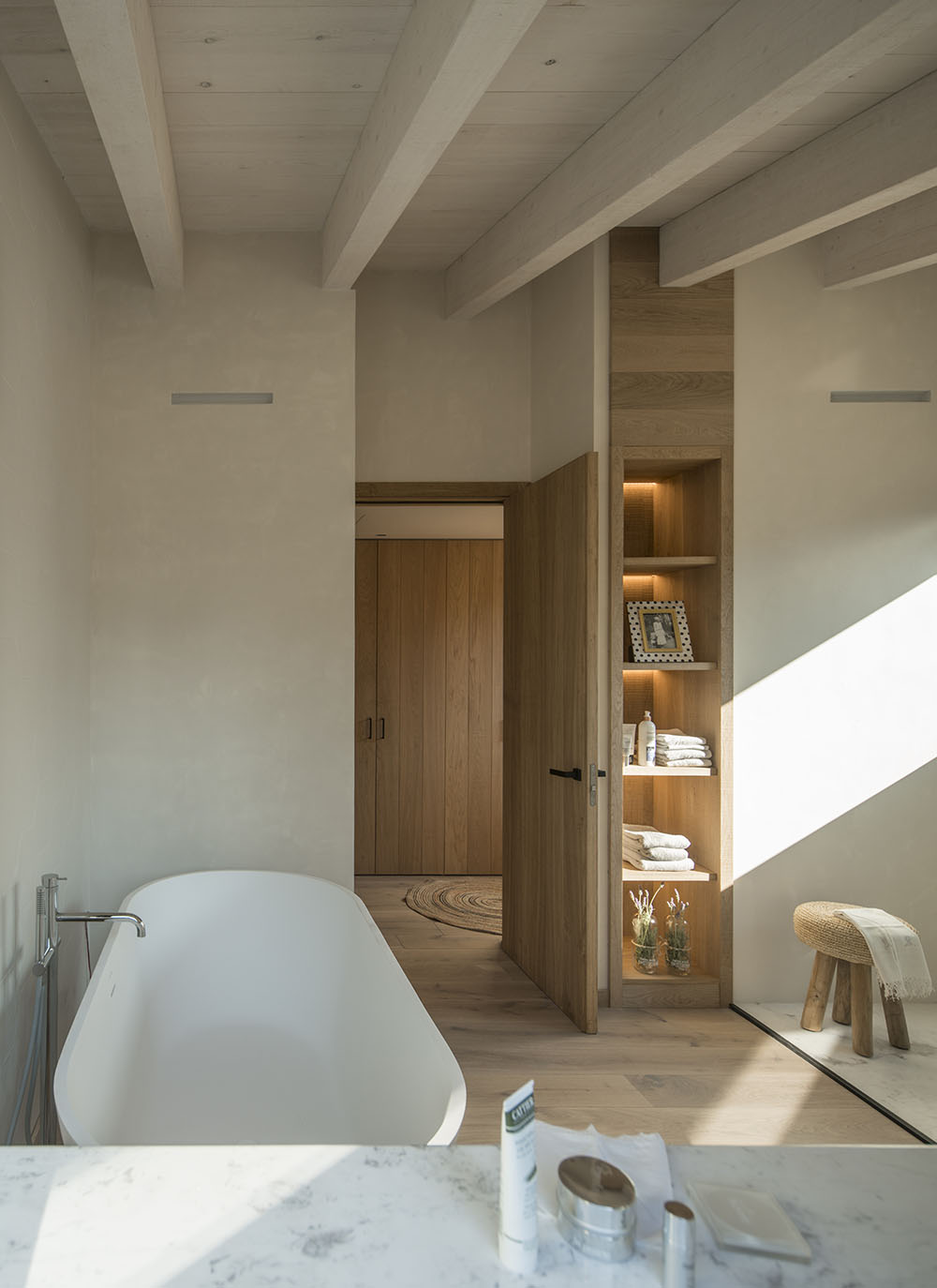 The narrow storage shelving features recessed lighting.