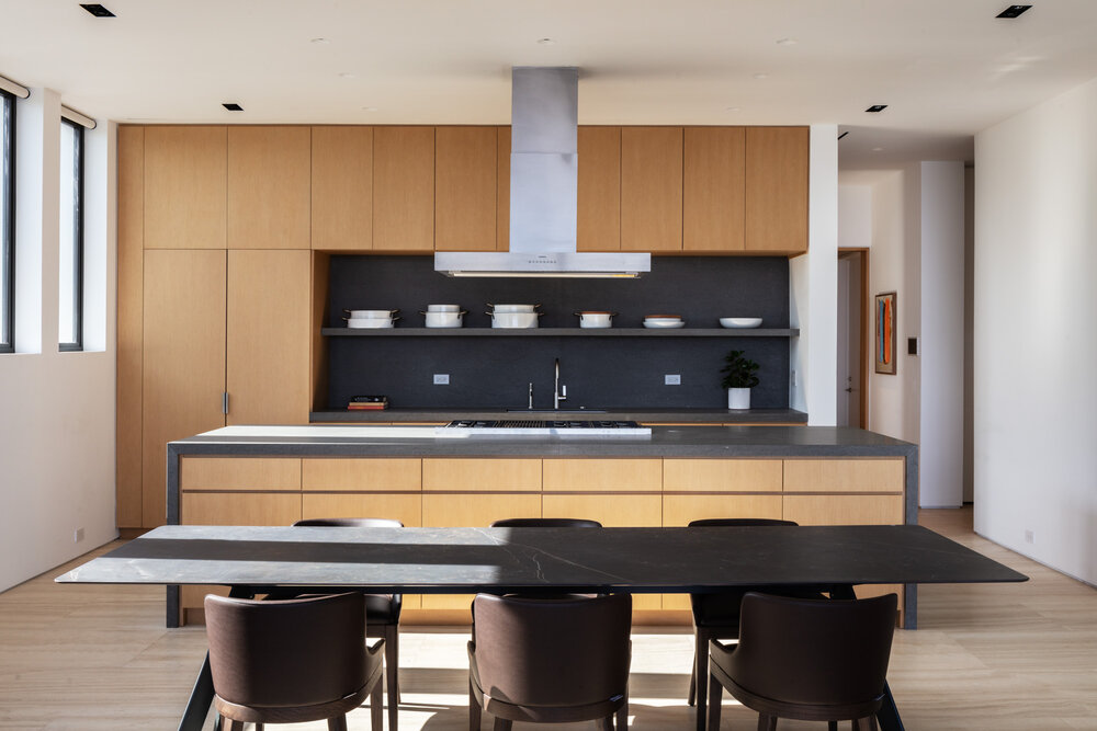 The kitchen has expansive storage inside the custom wooden cabinetry and the matching island