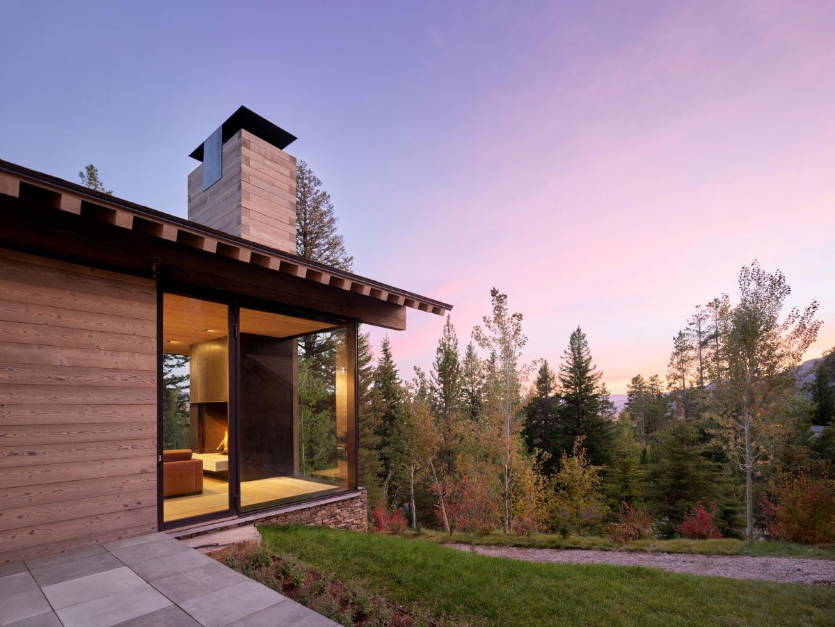 The sloping landscape envelops the house and extends along its walls, causing certain areas to be built into the land