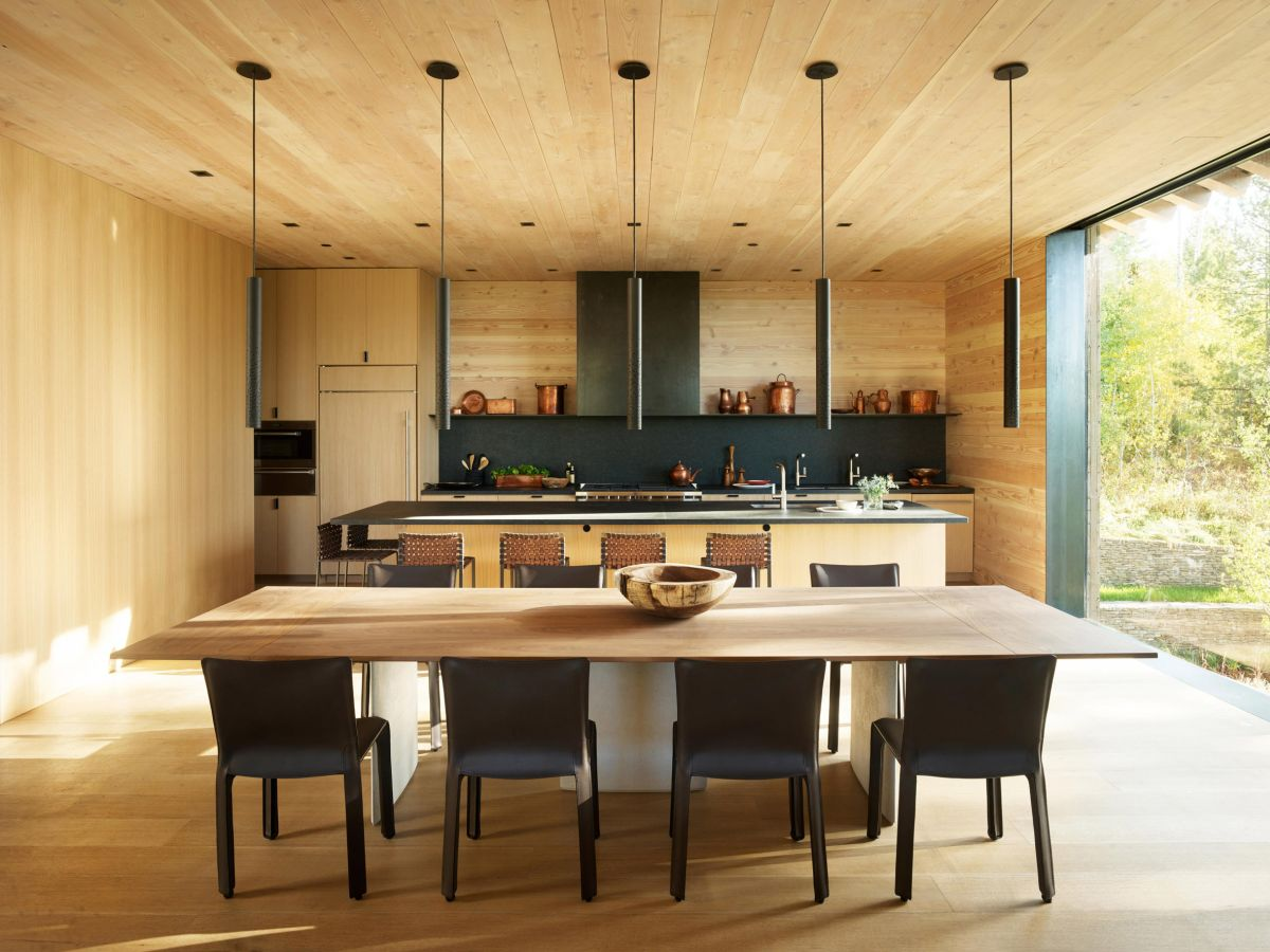 The kitchen and dining area are combined into an open space, with wood all over the floor, walls and ceiling