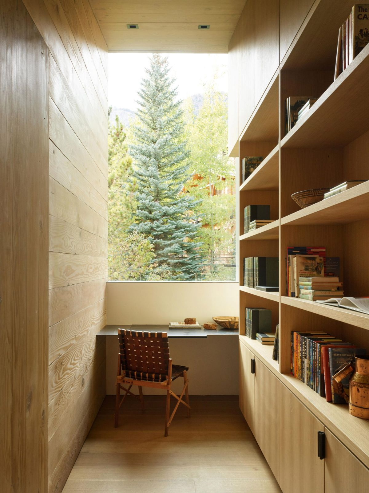 There's also a little nook with a desk in front of a big window and bookshelves along the wall