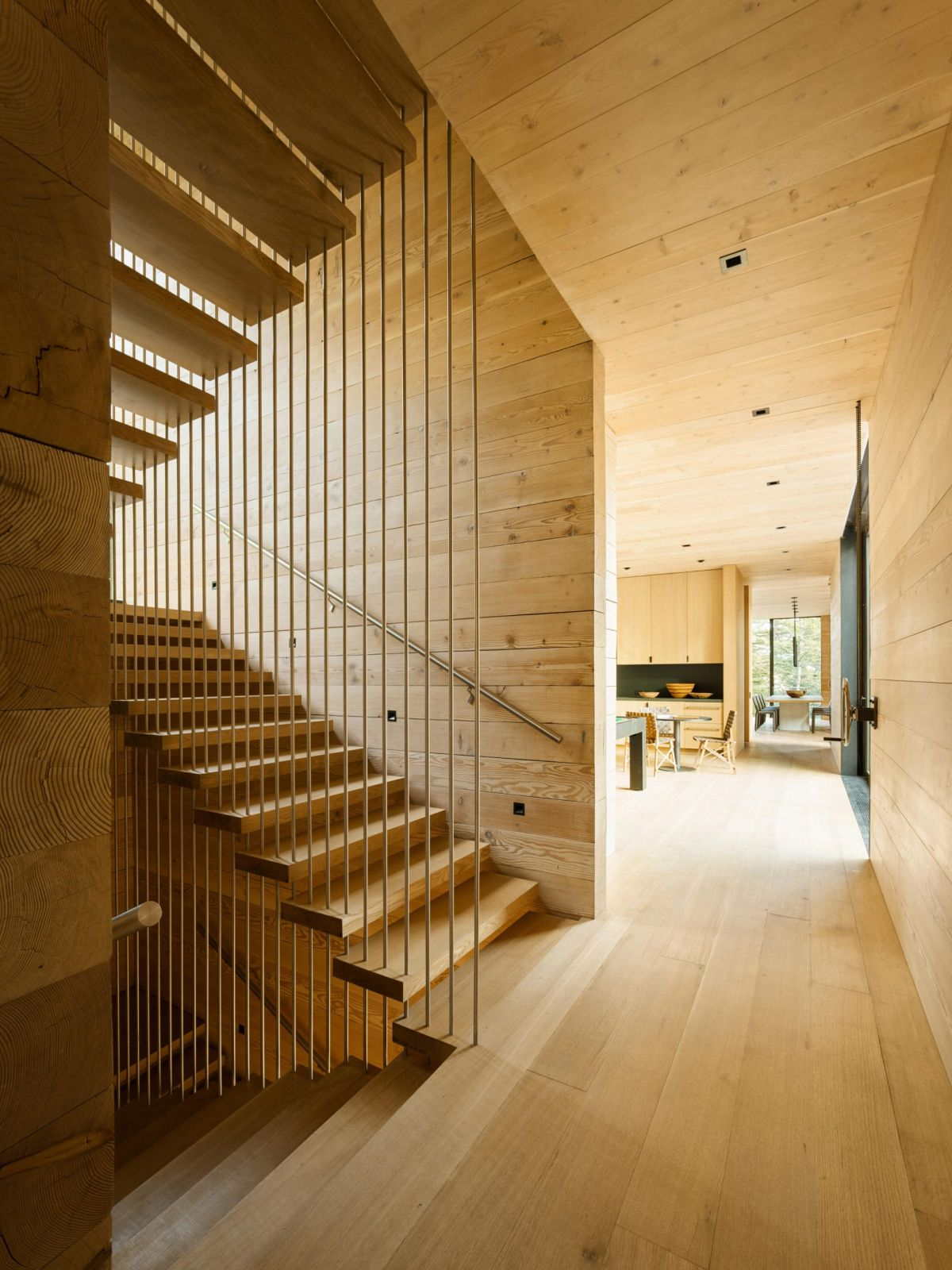 The floors are connected by a wooden staircase with thin metal rods as railings