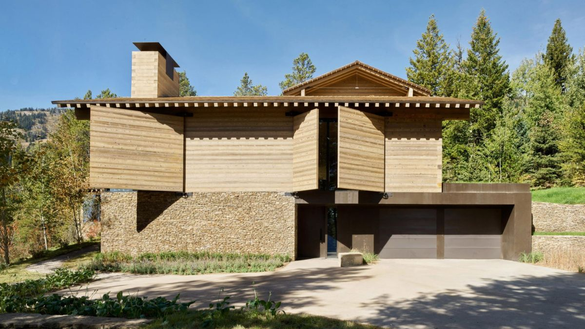The ground floor facade features a stone wall which adds texture to the design and contrasts with the wood paneling