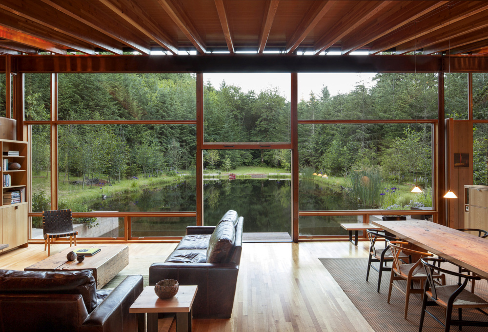 The South-facing side of the house is fully glazed and gets a panoramic view over the pond