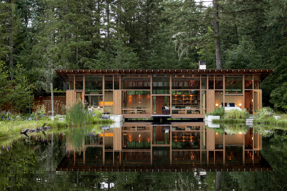 The main house has a linear floor plan which stretches across this side of the pond like a bridge