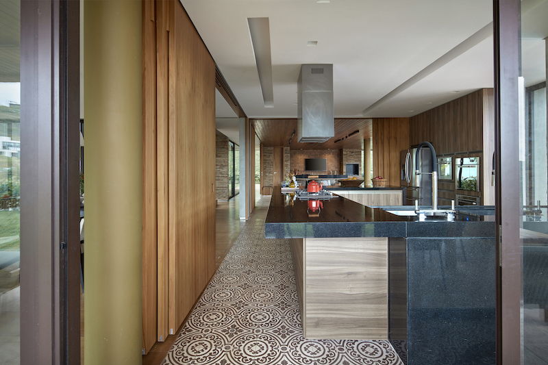The kitchen is situated at the center of the house, being open to adjacent spaces on all four sides