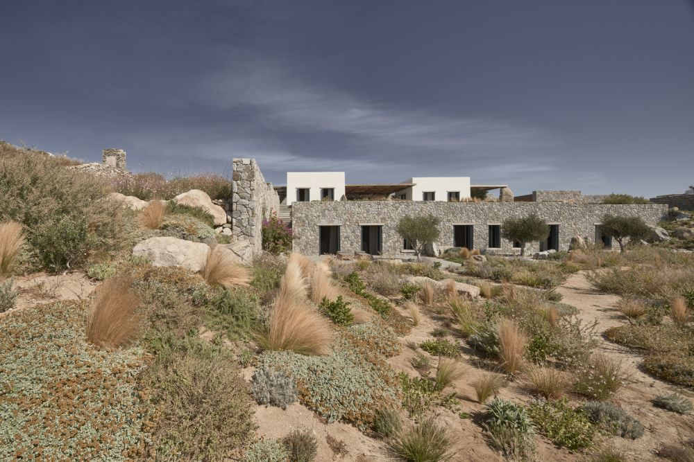 The exterior stone walls which surround the house create a protective shell and disguise the structure as part of the landscape