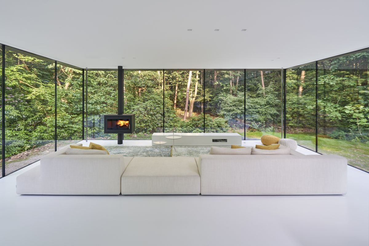 The views of the forest are maximized by the full-height windows and the minimalist interior decor