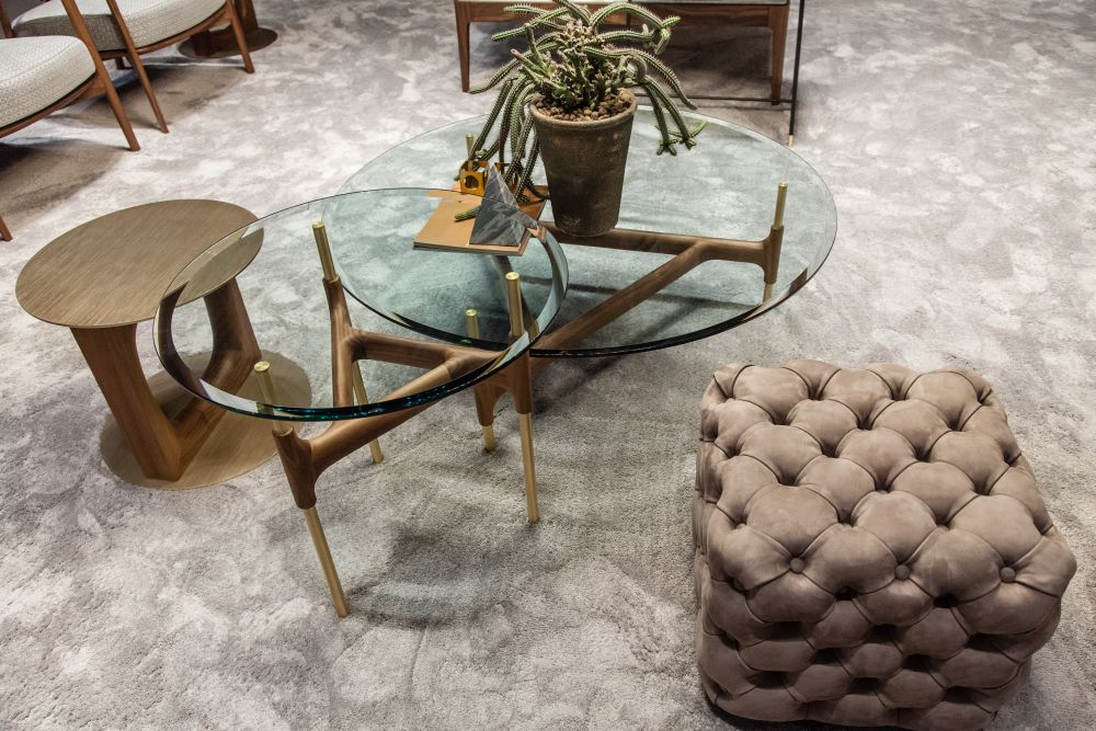The Joint coffee table features a base made of brass and canaletta walnut and a tempered glass top