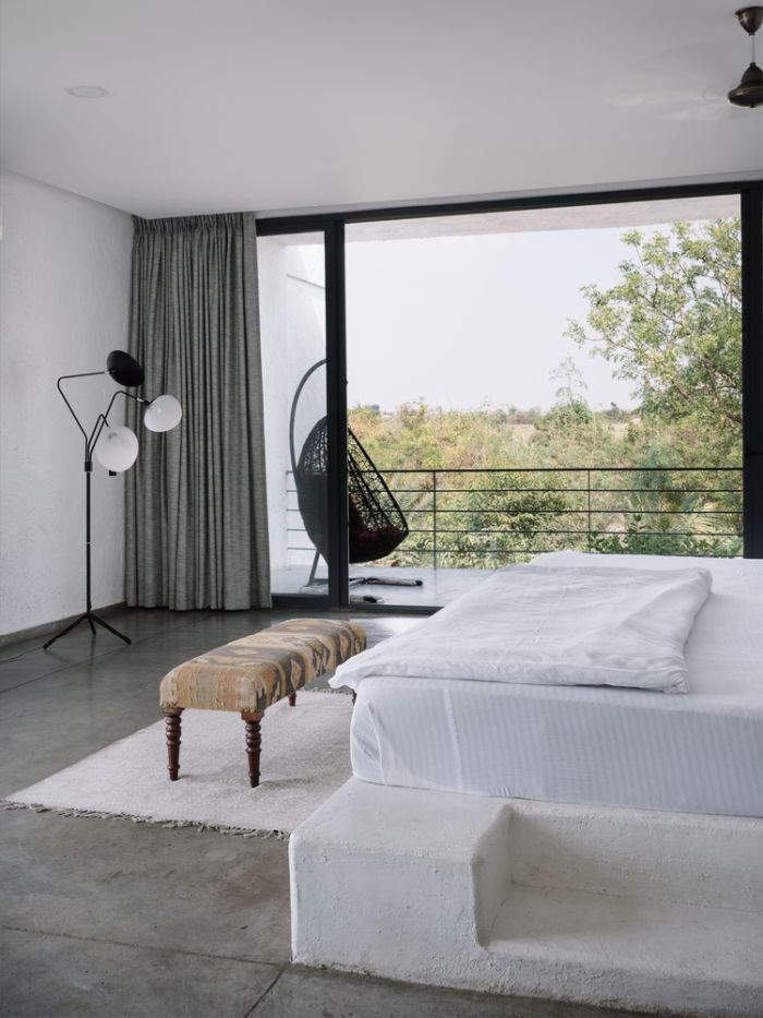 This cozy bedrooms has its own little balcony overlooking the dense vegetation outside