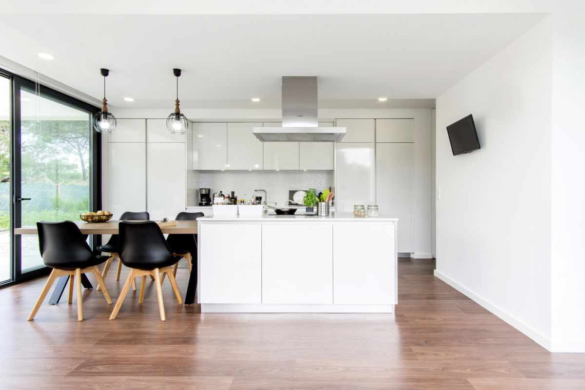 The kitchen has an island with a dining table extension, an ideal combo for modern spaces designed for entertainment