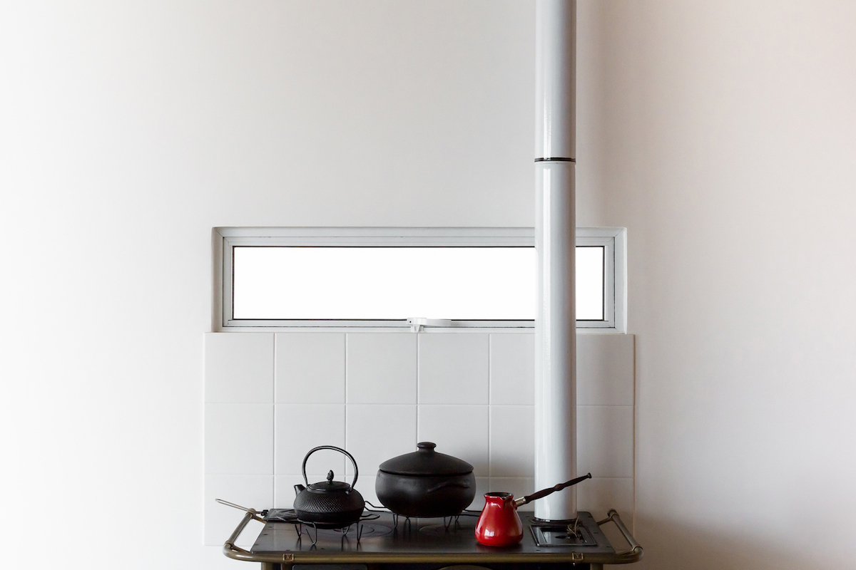 Some elements such as the stove add a touch of rusticity to the space and contrast with the rest of the decor