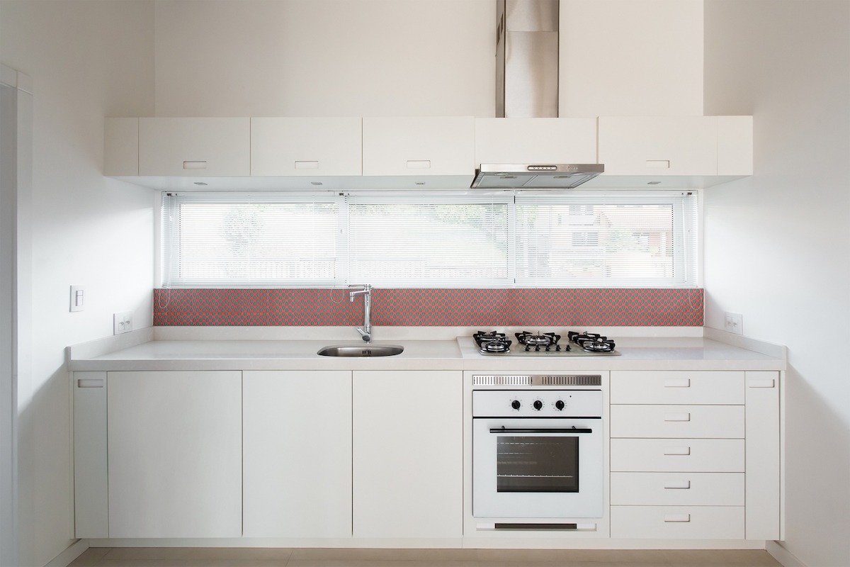 The kitchen has a low backsplash with red details matching the hallway decor