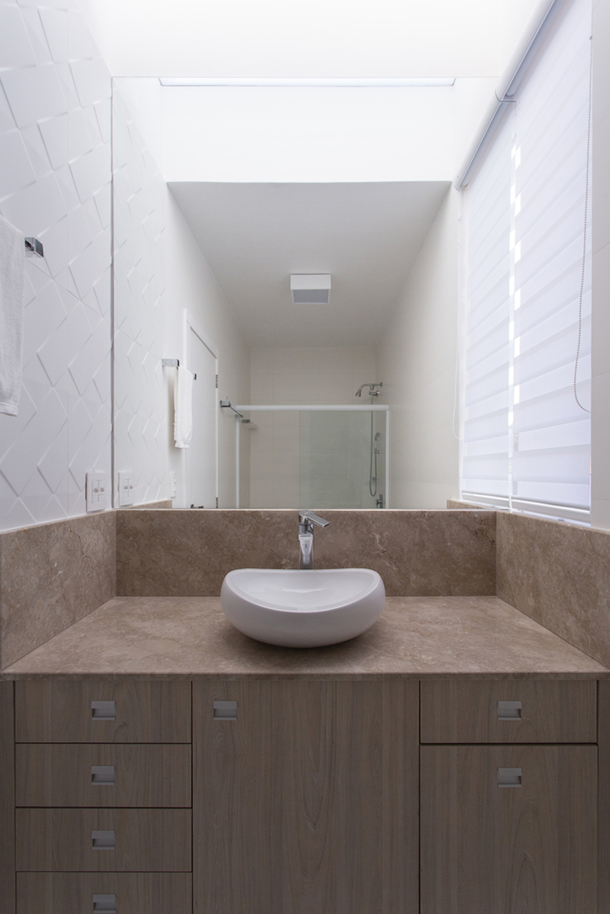 A large mirror visually enlarges the small bathroom while the textured tiles give it character