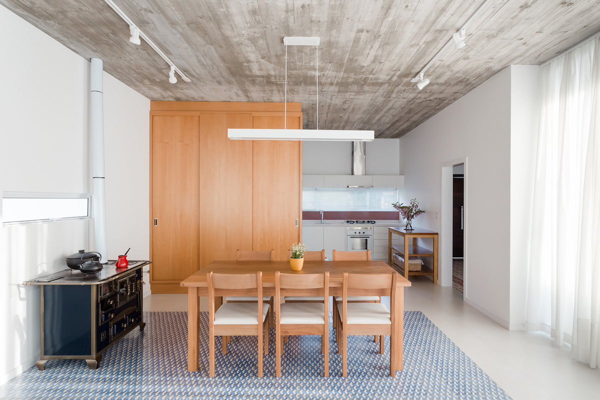 The dining area feels very home-like and cozy, featuring wooden furniture and a patterned floor