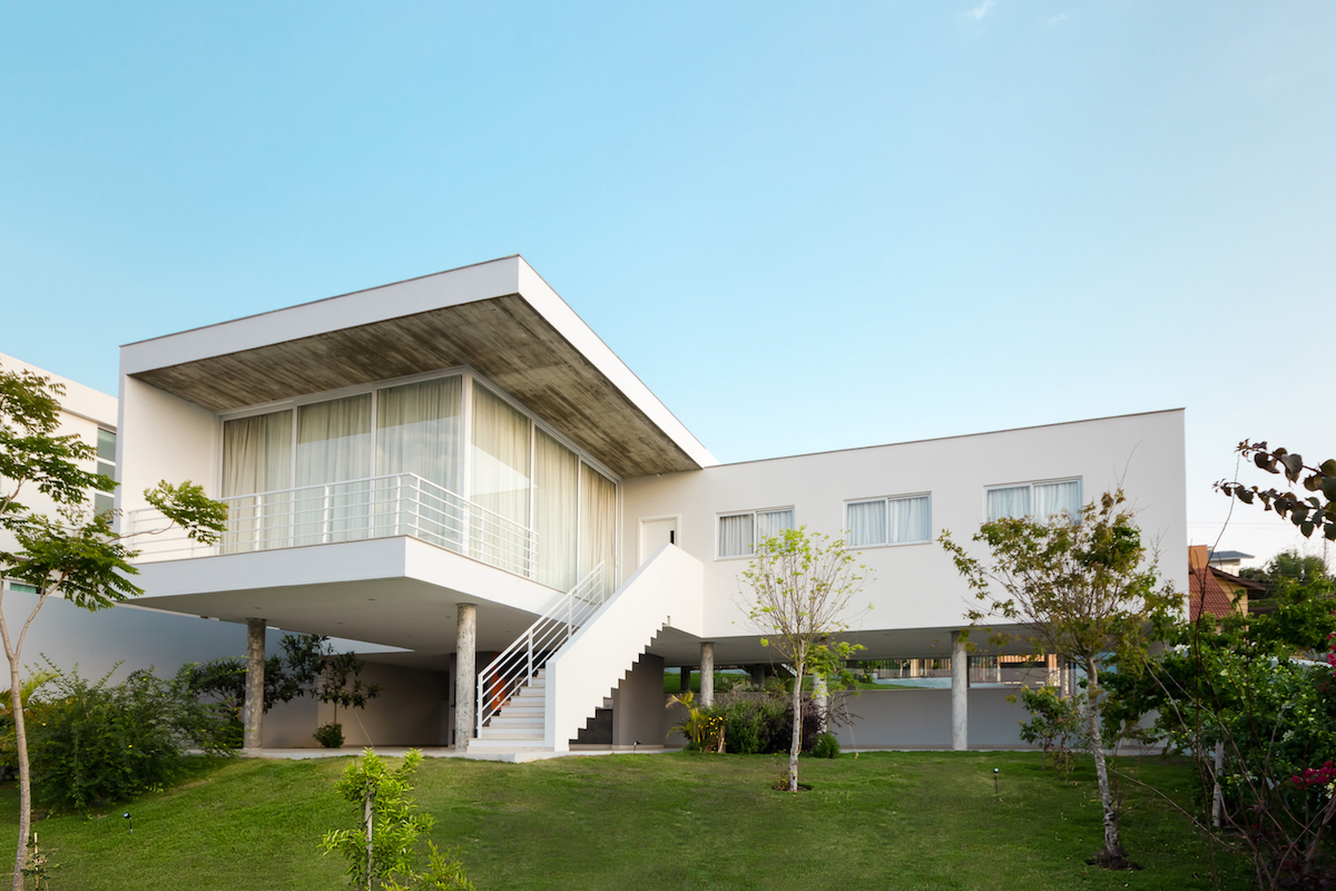 A white exterior staircase leads to the upper floor where all the main spaces are situated