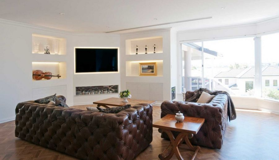 White living room with brown leather sofa and built in tv