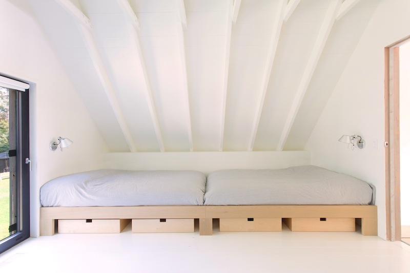 The upstairs sleeping area is open and cozy, sheltered under the gabled roof and with a very minimal decor