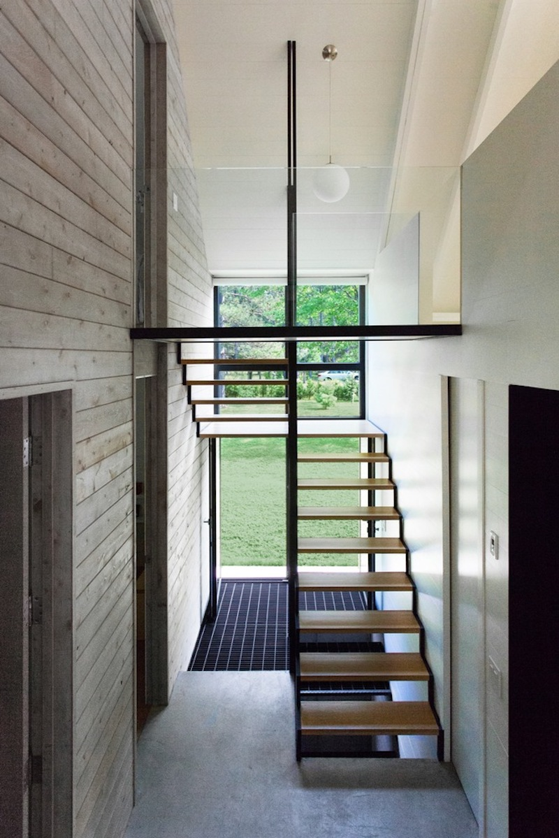 The sleeping area on the second floor can be accessed via a staircase with a simple and clean design